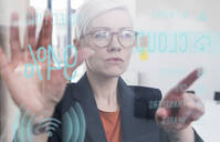Businesswoman touching glass wall with data in office - UUF17905