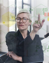 Businesswoman touching glass wall with data in office - UUF17908