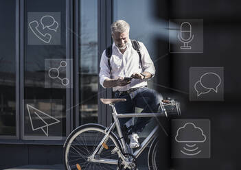 Smiling mature businessman with bicycle using cell phone for messaging in the city - UUF17917