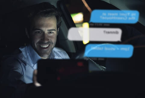 Smiling businessman using cell phone for messaging i in car at night - UUF17923