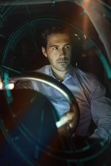 Businessman in car at night surrounded by virtual tachometer - UUF17926