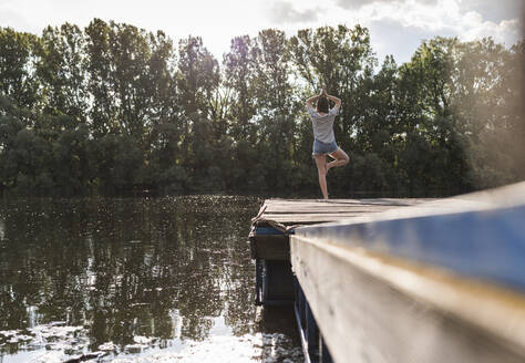 Young woman standing in yoga pose on jetty at a remote lake - UUF17929