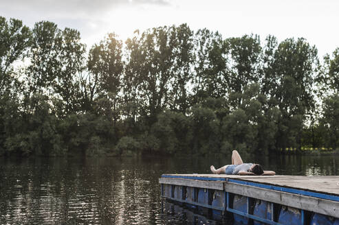 Relaxed woman lying on jetty at a remote lake - UUF17944