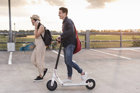 Happy young couple with cell phone, longboard and electric scooter on parking deck - UUF17959