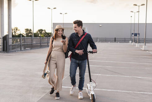 Happy young couple with cell phone, longboard and electric scooter on parking deck - UUF17962