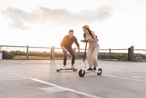 Young man and woman riding on longboard and electric scooter on parking deck at sunset - UUF17968