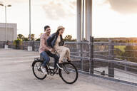 Happy young couple together on a bicycle on parking deck - UUF17974