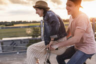 Happy young couple together on a bicycle on parking deck at sunset - UUF17977