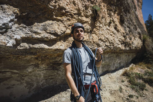 Climber with climbing rope in front of rock wall - RSGF00223