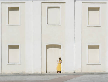 Side view of woman using mobile phone while standing by building in city - AHSF00570