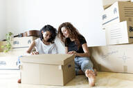 Two friends moving into new home opening cardboard box - JPTF00218