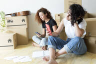 Two friends moving into new home using cell phones - JPTF00221