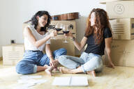 Two friends moving into new home clinking red wine glasses - JPTF00224