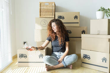 Young woman sitting in new home with glass of red wine - JPTF00227