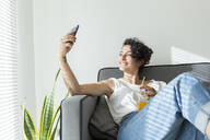 Smiling young woman sitting on couch with a soft drink taking a selfie - JPTF00233