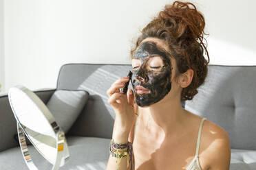 Young woman applying facial mask at home - JPTF00236