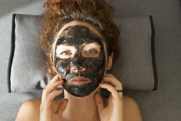Portrait of young woman lying down wearing facial mask - JPTF00239