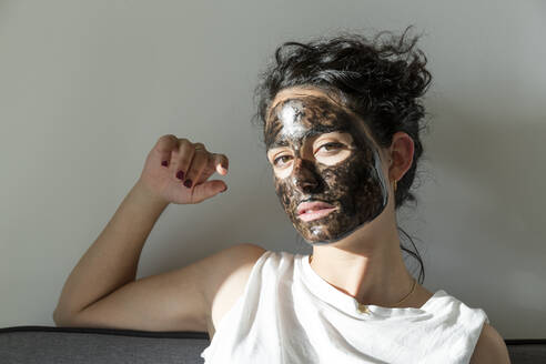 Portrait of young woman wearing facial mask at home - JPTF00245