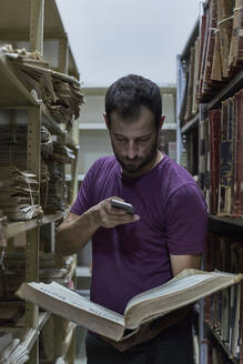 Man taking pictures of an old book at National library, Maputo, Mocambique - VEGF00335