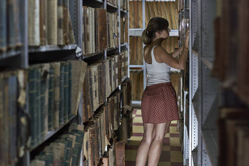 Back view of woman checking old books at National library, Maputo, Mocambique - VEGF00341