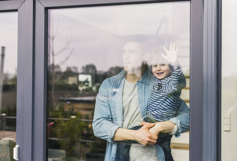Father holding laughing son, looking out of window - UUF18005