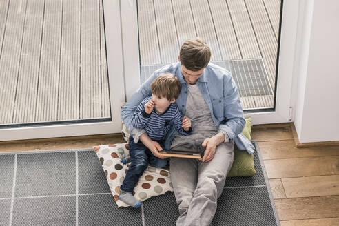 Father and son sitting on floor, using digital tablet - UUF18029
