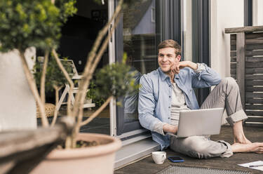 Man sitting on terrace, using laptop - UUF18038