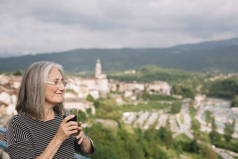 Relaxed senior woman with glass of coffee on her roof terrace, Belluno, Italy - ALBF00898