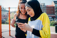Calisthenics class at outdoor gym, two young women looking at smartphone - CUF51680