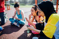 Calisthenics class at outdoor gym, young women sitting looking at smartphones and eating fruit - CUF51683