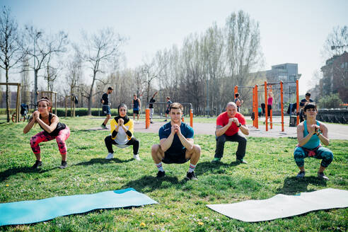 Calisthenics class at outdoor gym, women and men practicing yoga squatting pose - CUF51710