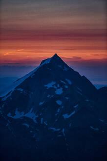 Mountain summit, orange glow on horizon in background, Saas-Fee, Valais, Switzerland - CUF51755