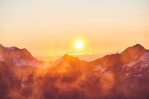 Sun glowing on horizon over mountain range, Saas-Fee, Valais, Switzerland - CUF51758