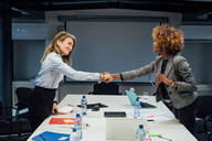 Business partners shaking hands at meeting in office - CUF51791