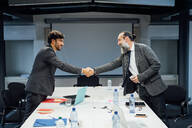 Business partners shaking hands at meeting in office - CUF51797