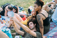 Group of friends relaxing, taking selfie at picnic in park - CUF51896