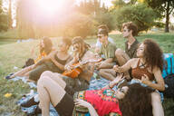 Group of friends relaxing, playing guitar at picnic in park - CUF51902