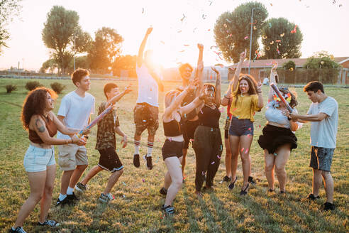 Group of friends dancing, playing with confetti in park - CUF51914