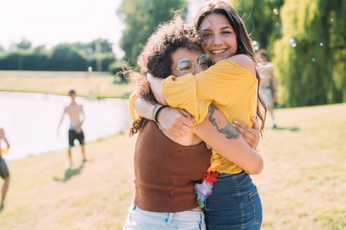 Friends hugging in park - CUF51917