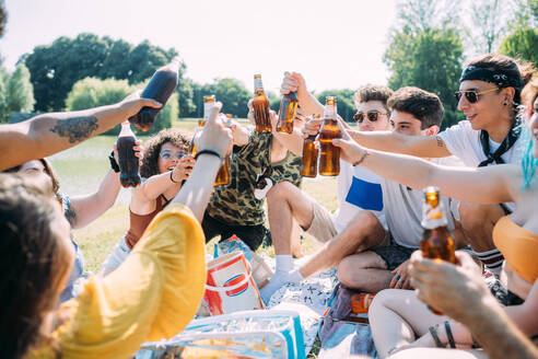 Group of friends relaxing, toasting soft drinks at picnic in park - CUF51920