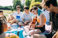 Group of friends relaxing, playing guitar at picnic in park - CUF51926