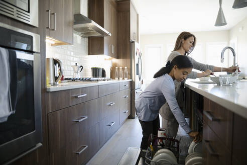 Mother and daughter doing dishes in kitchen - HEROF36815