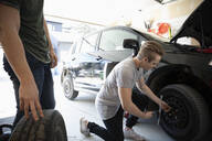 Teenage boy changing car tire in garage - HEROF36833