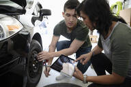 Mother and son with digital tablet learning to change car tire - HEROF36845