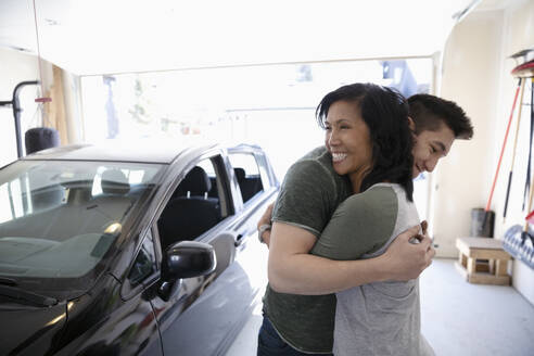 Happy mother and teenage son hugging in garage - HEROF36848