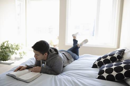 Teenage boy reading Bible on bed - HEROF36878