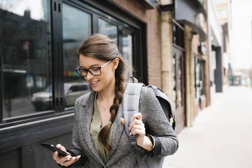 Businesswoman with backpack using smart phone on urban sidewalk - HEROF36911