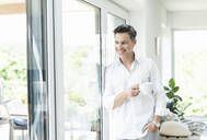 Mature man leaning on window, drinking coffee at home - UUF18085