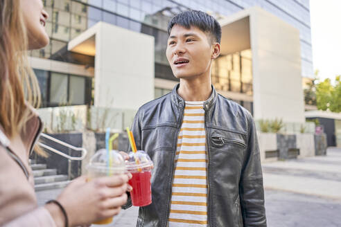 Portrait of young man with soft drink talking to his girlfriend - DVGF00014