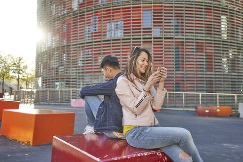 Couple sitting back to back using cell phones, Barcelona, Spain - DVGF00041